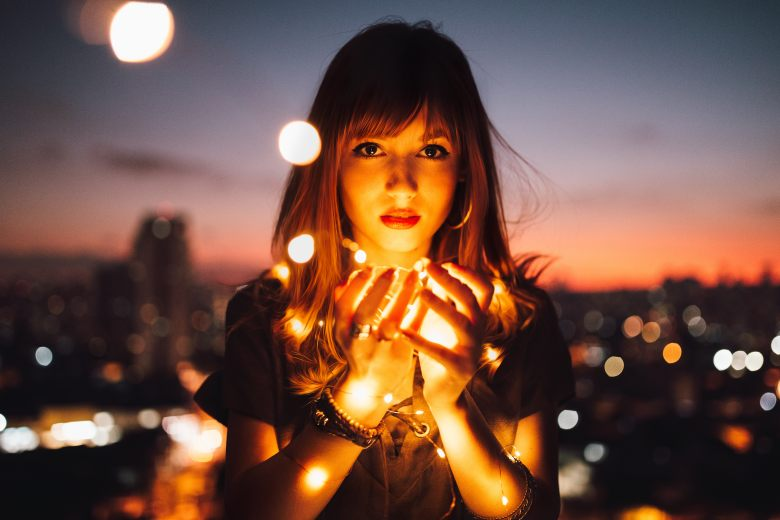Woman holding magic lights in her hands.